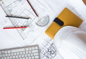 Image of blueprints with level pencil and hard hat on table.